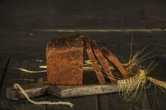 Pain fait maison frais avec la transitoire de blé entier sur un fond en bois noir Pain frais avec une oreille de blé image stock