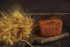 Pain fait maison frais avec la transitoire de blé entier sur un fond en bois noir Pain frais avec une oreille de blé photographie stock