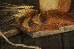 Pain fait maison frais avec la transitoire de blé entier sur un fond en bois noir Pain frais avec une oreille de blé photos stock
