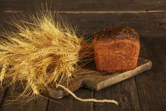 Pain fait maison frais avec la transitoire de blé entier sur un fond en bois noir Pain frais avec une oreille de blé photo libre de droits