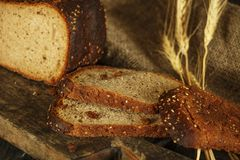 Pain fait maison frais avec la transitoire de blé entier sur un fond en bois noir Pain frais avec une oreille de blé photos libres de droits
