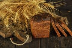 Pain fait maison frais avec la transitoire de blé entier sur un fond en bois noir Pain frais avec une oreille de blé images stock