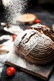 Pain, farine et tomates fraîchement cuits au four sur un conseil en bois sur une table Images libres de droits