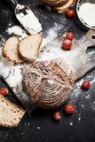 Pain, farine et tomates fraîchement cuits au four sur un conseil en bois sur une table Photographie stock libre de droits