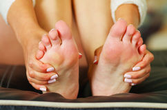 Pain in the foot, auto massage of both female feet. Pain in the foot. Massage of female feet. Pedicure Stock Photos