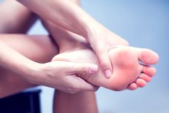 Woman hand holding foot with pain, health care and medical conce. Pain in the foot, girl holds her hands to her feet, foot massage, cramp, muscular spasm, red royalty free stock images