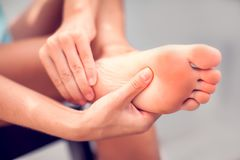 Woman hand holding foot with pain, health care and medical conce. Pain in the foot, girl holds her hands to her feet, foot massage, cramp, muscular spasm, red stock image