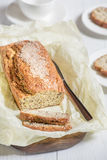 Pain fraîchement cuit au four avec les graines de sésame sur un conseil en bois sur un lig Photographie stock