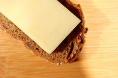 Pain fraîchement cuit au four de multi-grain avec du fromage sur le fond en bois Photo stock