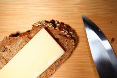 Pain fraîchement cuit au four de multi-grain avec du fromage sur le fond en bois Images stock