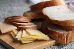 Pain frais coupé en tranches et différentes variétés découpées en tranches de fromage sur W Photos libres de droits