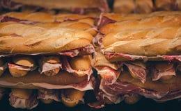 Pain français avec le jamon espagnol Jambon espagnol traditionnel Tranches minces du jamon d'Iberico entre en deux pièces Photos stock