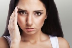 Pain. The girl suffers from terrible headaches and gripping her. Closeup is a natural portrait of beautiful woman with big dark eyes. Professional makeup. A Stock Images