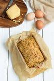Pain gratuit de beurre d'oeufs, de fromage et de gluten fait maison, brioche, dans le plat de cuisson sur un fond en bois blanc c Images libres de droits