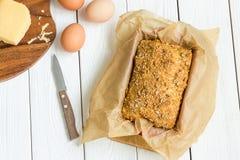 Pain gratuit de beurre d'oeufs, de fromage et de gluten fait maison, brioche, dans le plat de cuisson sur un fond en bois blanc c Photographie stock libre de droits