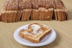 Pain grillé beurré avec le pain Defocused à l'arrière-plan Image stock