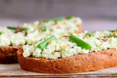 Pain grillé de guacamole d'avocat avec des épices et des oignons verts frais sur un conseil en bois Guacamole d'avocat sur la rec Images stock