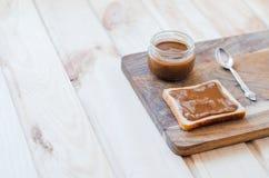 Pain grillé et pot avec le beurre d'arachide sur un conseil en bois photo stock