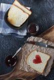 Pain grillé fait maison avec de la confiture de fraise dans la forme du coeur, petit déjeuner de jour de valentines Photos libres de droits