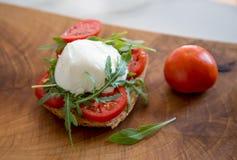 Pain grillé italien de style avec du fromage de pain léger, d'arugula, de tomate et de mozzarella Photo stock