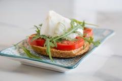 Pain grillé italien de style avec du fromage de pain léger, d'arugula, de tomate et de mozzarella Images stock