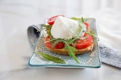 Pain grillé italien de style avec du fromage de pain léger, d'arugula, de tomate et de mozzarella Photo libre de droits