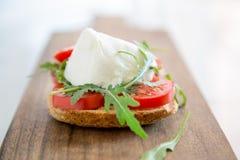 Pain grillé italien de style avec du fromage de pain léger, d'arugula, de tomate et de mozzarella Photos stock