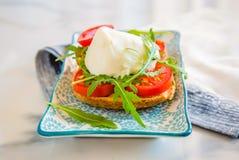 Pain grillé italien de style avec du fromage de pain léger, d'arugula, de tomate et de mozzarella Image libre de droits