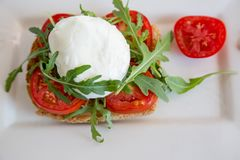 Pain grillé italien de style avec du fromage de pain léger, d'arugula, de tomate et de mozzarella Photographie stock libre de droits