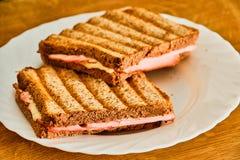 Pain grill? avec du jambon et le fromage du plat blanc photos stock