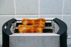 Pain grill? dans un grille-pain Grille-pain avec des pains grillés savoureux de petit déjeuner sur la table photos stock