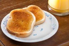 pain grillé et jus d'orange pendant le matin Photos stock