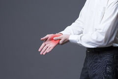 Pain in hand, joint inflammation, carpal tunnel syndrome on gray background. Pain in hand, joint inflammation, carpal tunnel syndrome, studio shot with red dot royalty free stock photos