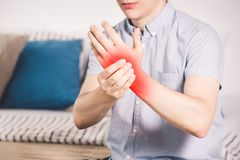 Pain in hand, man suffering from carpal tunnel syndrome at home. Painful area highlighted in red stock image
