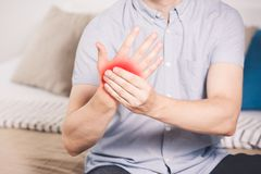 Pain in hand, man suffering from carpal tunnel syndrome at home. Painful area highlighted in red stock photography