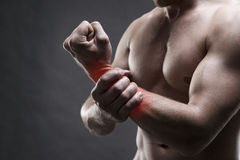 Pain in the hand. Muscular male body. Handsome bodybuilder posing on gray background Royalty Free Stock Photo