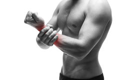 Pain in the hand. Muscular male body. Handsome bodybuilder posing in studio. Isolated on white background with red dot Royalty Free Stock Photos