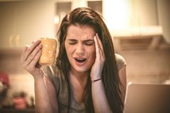 Pain headache . Young woman sitting in kitchen. Pain headache . Young woman sitting in kitchen and holding cup of coffee Royalty Free Stock Image