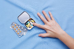 Pain from illness with hand trying to take pills Stock Photography