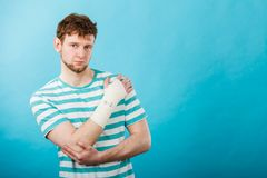 Man with painful bandaged hand. Pain and injury concept. Young man holds bandaged hand. Injured part of body. Medicine and healthcare royalty free stock photography