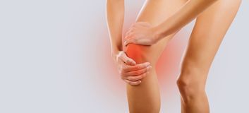 Pain, injury to the knee. A woman holds her knee with her hand stock photo