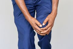 Pain in the knees of a man. Pain In Knee. Close-up African Male Leg With Painful Kneeson on gray background. Man Feeling Joint Pain, Having Health Issues And royalty free stock photo