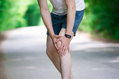 Pain in knee, joint inflammation, massage of male leg, injury while running, trauma during workout. Outdoors concept royalty free stock photography