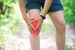 Pain in knee, joint inflammation, massage of male leg, injury while running, trauma during workout. Outdoors concept stock photos