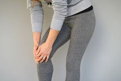 Pain in the knees of a woman. Pain In Knee. Close-up Female Leg With Painful Knees. Woman Feeling Joint Pain, Having Health Issues And Touching Leg With Hands Stock Photography