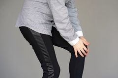 Pain in the knees of a woman. Pain In Knee. Close-up Female Leg With Painful Knees isolated on gray background. Woman Feeling Joint Pain, Having Health Issues Royalty Free Stock Images