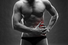 Pain in the left side. Muscular male body. Handsome bodybuilder posing on gray background. Black and white photo with red dot Royalty Free Stock Photos