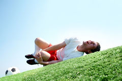Pain in leg. Image of soccer player lying down and shouting in pain Royalty Free Stock Image
