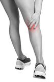 Pain in the Leg. Female jogger with pain in her lower leg, black and white, isolated in white, red spot around painfull area Royalty Free Stock Photos