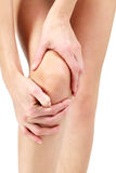 Pain in a leg. Woman holding sore knee, white background Royalty Free Stock Photography